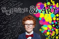 Smart child boy in suit and glasses on science and arts occupations pattern background.  royalty free stock photography