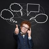Smart child boy with thumb up and empty speech clouds bubbles on chalkboard.  royalty free stock photos