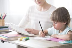 Smart child doing homework. At a desk with support of a tutor stock images