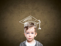Smart child in a drawn student hat royalty free stock photography