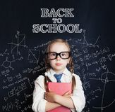 Smart child girl in glasses on chalk board background. Back to school concept stock photos