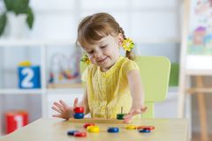 Little child girl plays in kindergarten in Montessori preschool class. stock photography