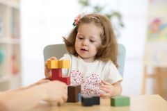 Little child girl plays in kindergarten in Montessori preschool class. Smart child girl plays in kindergarten in Montessori preschool class royalty free stock photography