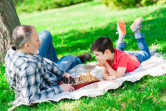 Smart child and grandparent are resting in the nature Royalty Free Stock Photo