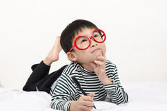 Smart child lying on bed Stock Images