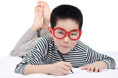 Smart child lying on bed  writing and thinking Stock Photo