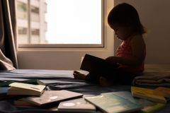 Smart child reading books on her bed. Learning how to read. royalty free stock photos