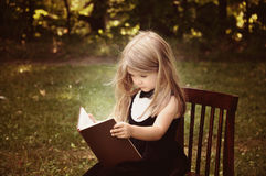 Smart Child Reading Education Book Outside. A smart little girl is reading an old book in nature with trees in the background for an education or knowledge stock image