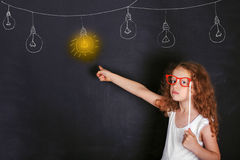 Smart child with red glasses points a finger at lighted lamp. Royalty Free Stock Images