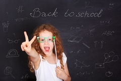 Smart child with red glasses showing gesture peace or victory ha. Nd triumph. Education and Leadership concept Royalty Free Stock Images