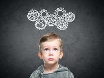 Smart child thinks of looking at gears Stock Images