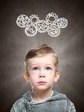 Smart child thinks of looking at gears stock photography