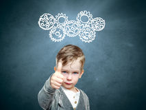 Smart child thinks of looking at gears stock photo
