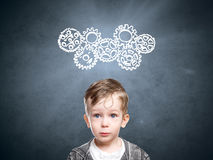 Smart child thinks of looking at gears Stock Photos