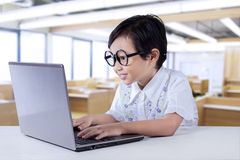 Smart child typing on laptop in the class Royalty Free Stock Photography