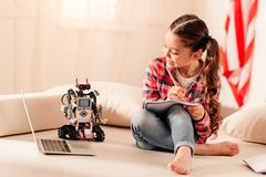Smart child writing her essay on robotic machines. Contemporary living. Educated young lady smiling while looking at her robot toy and writing an article about Royalty Free Stock Photography
