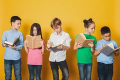 Smart children reading books near yellow wall royalty free stock images