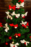 Smart Christmas tree decorated with red and cream-colored satin bow Royalty Free Stock Photos
