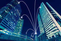 Smart city and internet line in blue tone, wireless communication network line on city commercial building background.  stock photography