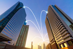 Smart city and internet line in blue tone, wireless communication network line on city commercial building background.  stock image