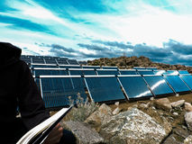 Smart and Clean Energy. Reading a book atop the Rocky hills of Sierra Nevada just beside some residing solar panels. Suggesting that clean energy and self Royalty Free Stock Image