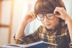 Smart clever boy fixing his glasses. Interesting book. Smart clever pleasant boy sitting at the table and fixing his glasses while reading a book stock photos