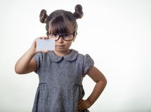 Smart or clever child holding discount white card in her hands. Kid with credit card. Little girl with glasses showing empty blank paper note copy space stock image