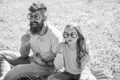 Smart and clever concept. Dad and daughter sits on grass at grassplot, green background. Child and father posing with. Eyeglases photo booth attributes at royalty free stock photography