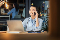 Smart confident doctor listening to her interlocutor. Important conversation. Smart nice confident doctor sitting in front of the laptop screen and listening to Stock Image