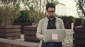 Grown businessman outside. Smart and confident guy working outside in a park on a laptop. Businessman sitting on a bench and doing business. Freelancer working stock footage