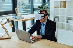 Smart confident man testing new technologies. Technological innovations. Smart pleasant confident man wearing 3d glasses and working on a laptop while testing Stock Images