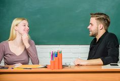 Smart and confident. Teacher and schoolmaster sitting at desk. Handsome man and pretty woman back to school. University. Or college students. High school stock photography