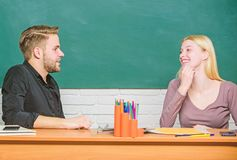 Smart and confident. Teacher and schoolmaster sitting at desk. Handsome man and pretty woman back to school. University. Or college students. High school stock image