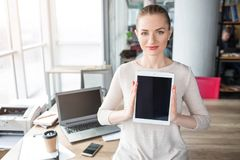 Smart and confident woman is looking to the camera and holding a tablet in it. The screen of the tablet is dark. Also stock photography
