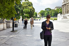 Smart and confident young woman striding through urban area Stock Image