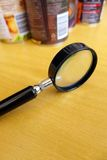 Smart consumer concept. Know what you eat ! - Smart consumer concept image.  A photograph showing a magnifying glass on a brown wooden table with some tinned can Stock Image