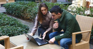 A smart couple is sitting at a terrace cafe and using a laptop stock video