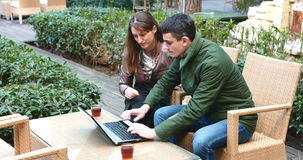 A smart couple is sitting at a terrace cafe and using a laptop stock video footage
