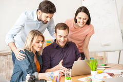 Smart creative team is discussing a project. Attractive young men is showing a presentation on laptop and explaining his ideas. His colleagues are standing and Royalty Free Stock Photography