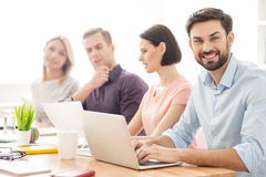 Smart creative team is planning a new project. Handsome young men is using a laptop for work. He is smiling and looking at camera with joy. His colleagues are Royalty Free Stock Image