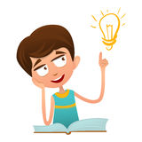 Smart cute baby boy sitting on a book and holding a finger up and over the lamp. Royalty Free Stock Images