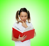 Smart cute girl reading from a red book Royalty Free Stock Image