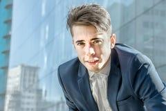 Smart, das hübsches junges Geschäftsmannporträt über Bürogebäudehintergrund schaut Stockfotografie