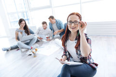 Smart delighted woman being a team leader. Great responsibility. Smart delighted positive women fixing her glasses and smiling while being a team leader stock images