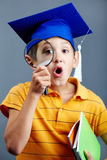 Smart detective. Portrait of curious boy in graduation hat looking through magnifying glass stock images