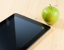 Smart digital tablet pc and green apple on wood table Royalty Free Stock Photography