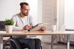 Smart disabled guy reading during breakfast Royalty Free Stock Image