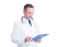 Smart doctor or medic analyzing document on clipboard Stock Images