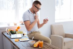 Focused attractive man examining biohacking drug. Smart drug. Earnest appealing smart man sitting on surface while touching chin and rising bottle Royalty Free Stock Photography