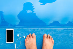 Smart with Earphone and foot on edge swimming pool. Stock Photography